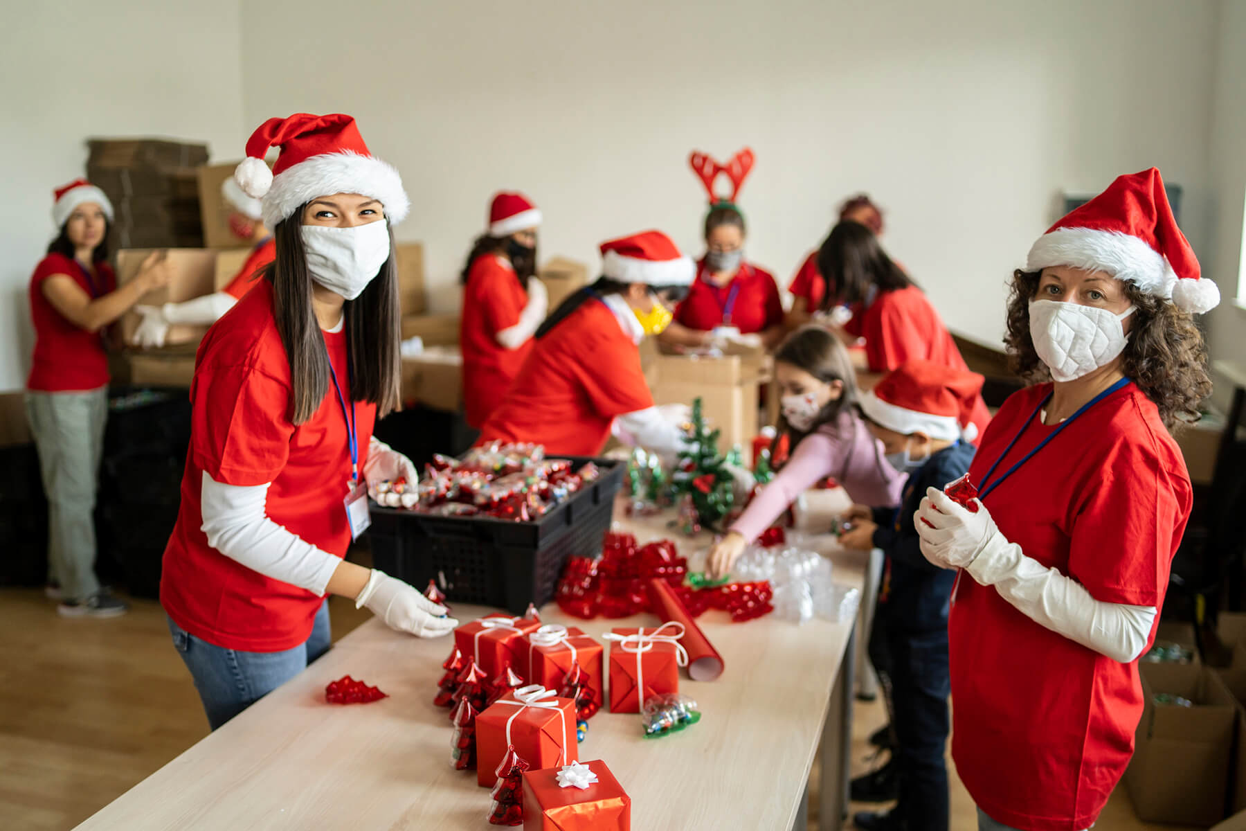 Volunteers with masks wrapping holiday gift donations