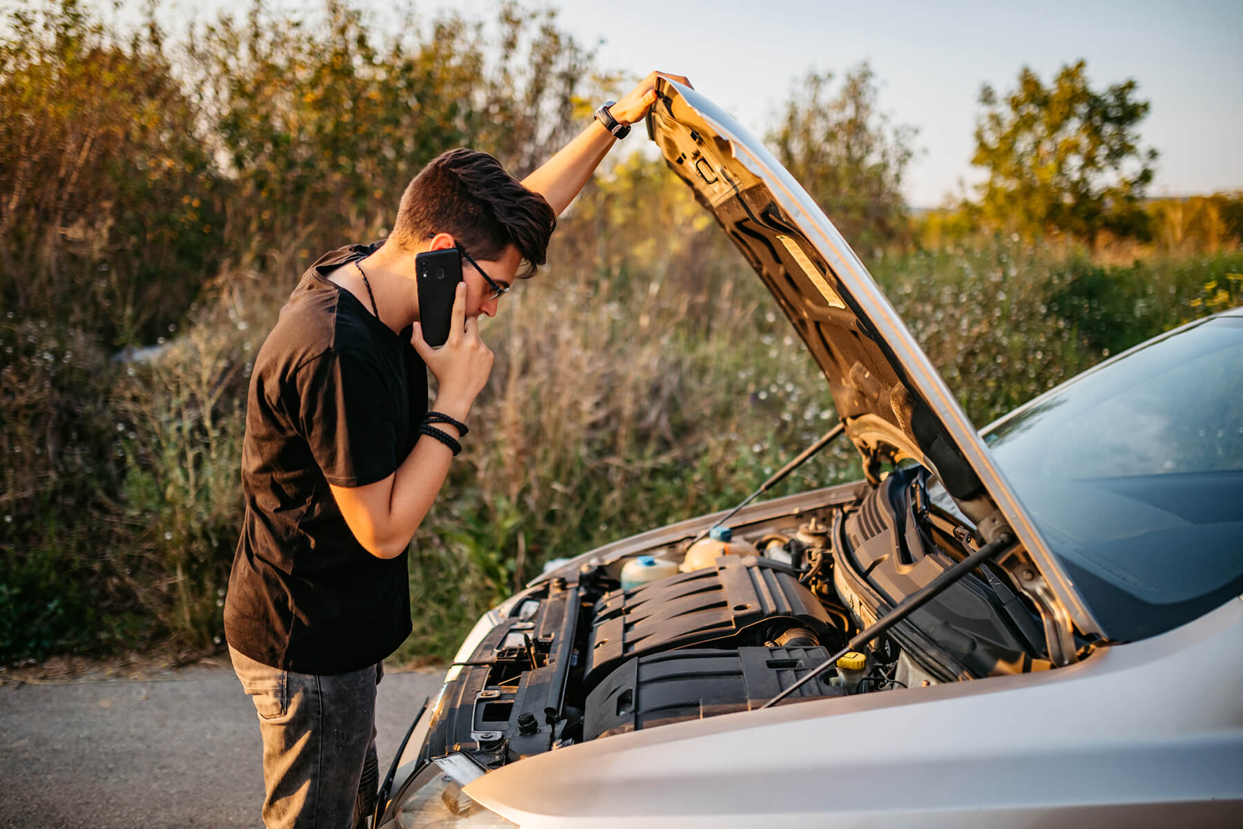 A young man looks under the hood of his car while making a call on his cellphone