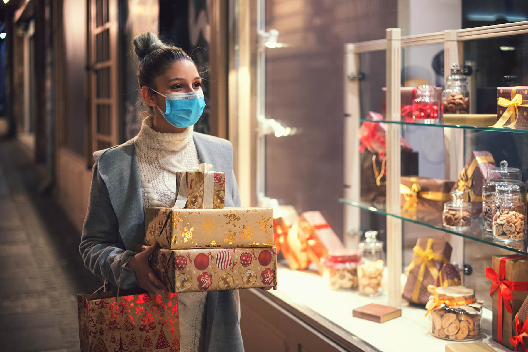 A woman wearing a facemask carries holiday gifts while window shopping
