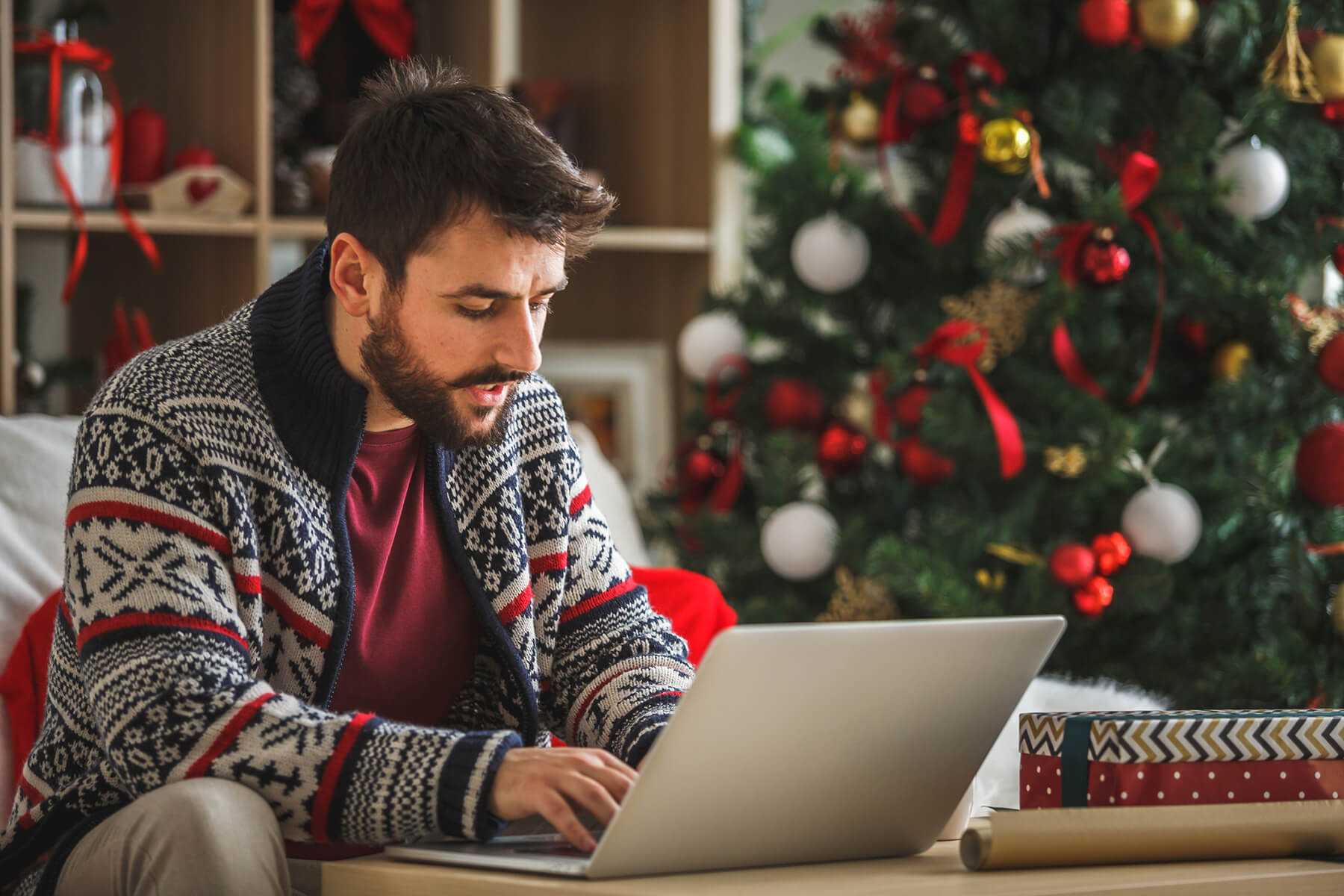 Man sits with a laptop in his living room, decorated for the holidays