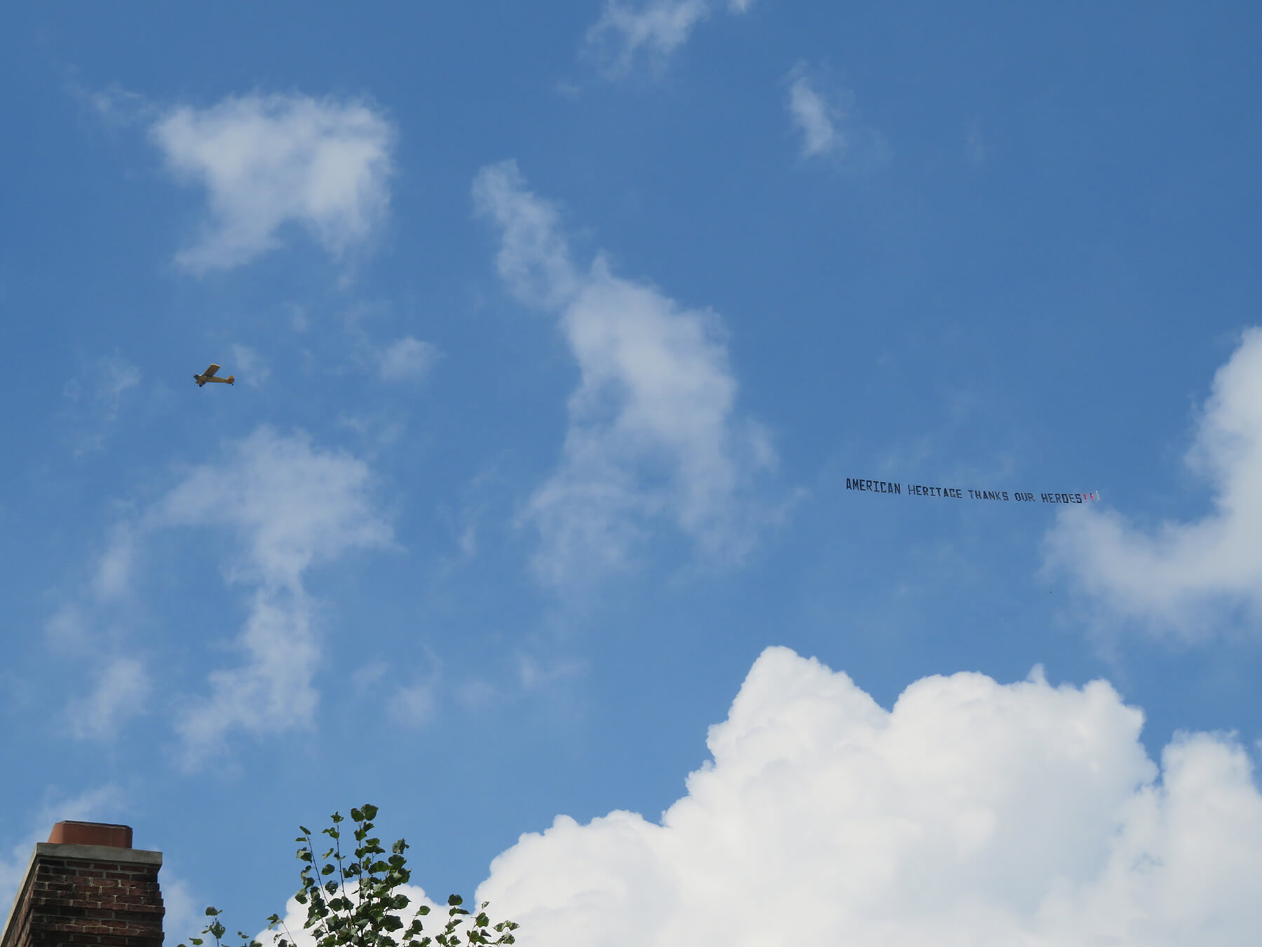 """Airplane with banner that says """"American Heritage Thanks Our Heroes"""" flies over American Heritage's campus."""